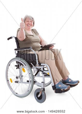 Senior sitting in wheelchair showing thumbs up while holding tablet device. All on white background.