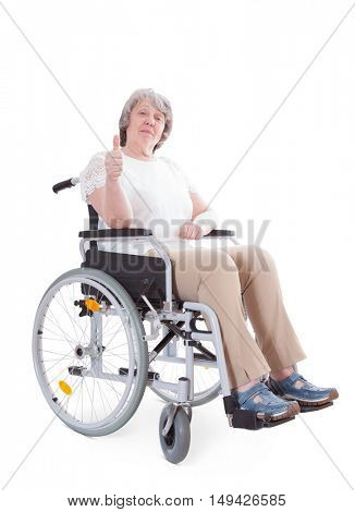 Senior sitting in wheelchair showing thumbs up. All on white background.