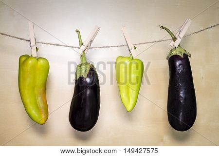 Eggplant And Paprika On Wooden Background Hanging On A Rope