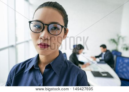 Face of young unsmiling Asian business lady in glasses