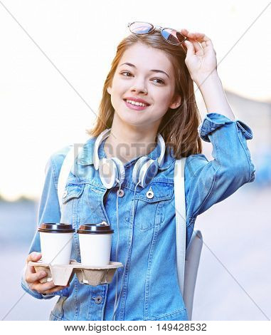 Young girl with cup of coffee outdoors