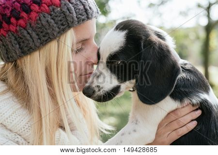 Young woman with cute puppy playing outdoor