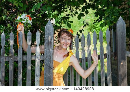 Young beautiful girl bride in a bright orange dress waving. Summer bouquet in hands of the bride. Decoration of flowers in their hair hairstyle. Hippie Bride. Sunny mood.