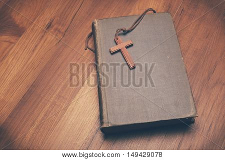Vintage tone of wooden Christian cross necklace on holy Bible with copy space