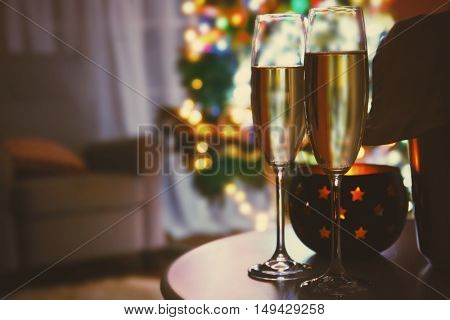 Two glasses of champagne on blurred background, close up view