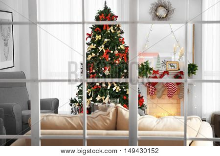 Cozy Christmas interior of living room with beautiful fir tree, view through window
