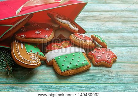 Delicious Christmas cookies with paper bag on wooden background