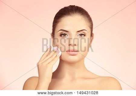 Beautiful young woman with face wipe on color background