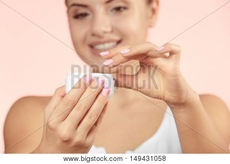 Jar of cream in female hands, close up