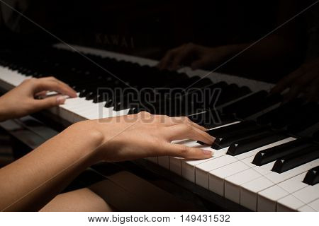 a woman's hand playing a piano, a music photo