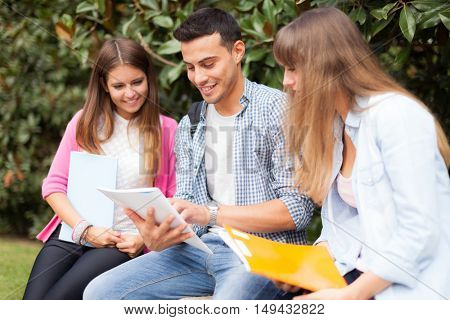 Outdoor portrait of three smiling students studying in a park