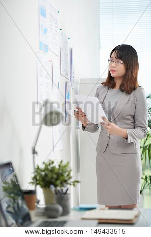 Financial manager analyzing charts and graphs on the wall