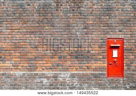 Red mail box in a brick wall