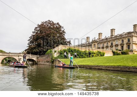 CAMBRIDGE UK - AUGUST 11 2015: Punting on the river Cam. Some companies and students hire punts to visitors and tourists. Cambridge is a university city and one of the top five universities in the world.