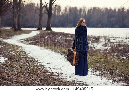 Woman walking in forest with old suitcase in wintertime. Image is intentionally toned.
