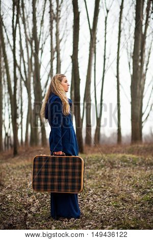 Woman walking in forest with old suitcase in wintertime.