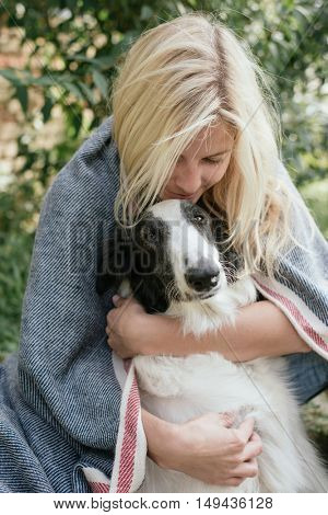 Young woman embracing her dog under a warm blanket