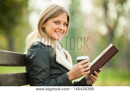 Young woman is reading book and drinking coffee to go.