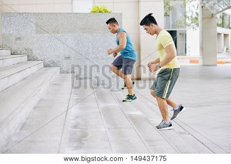 Side view of two athletes running on staircase
