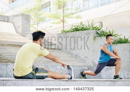 Fit men doing exercises for legs outdoors