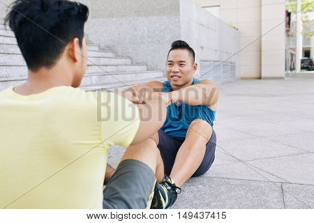 Vietnamese fit man working out with his friend outdoors