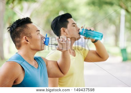 Asian joggers drinking fresh water after outdoor training