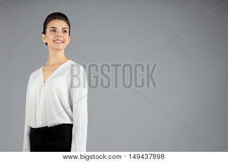 Beautiful businesswoman on gray background