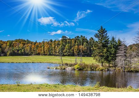 The sun is reflected in the water of the lake. Rocky Mountains on a sunny autumn day. The concept of active tourism and ecotourism