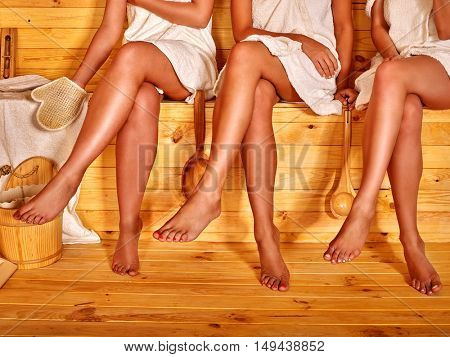 Low part of female feet in sauna. Group of women have relax.