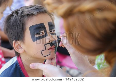 Young boy getting face painted as a creeper