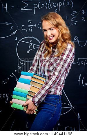 Portrait of a smiling student girl standing by a school blackboard with books. Education, high school, college.