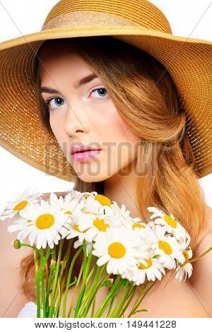 Summer inspiration. Romantic girl in a straw hat holds a bouquet of white daisies. Beauty, summer fashion. Isolated over white.