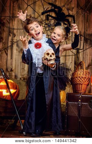 Two funny children in halloween costumes posing together in a wooden barn with pumpkins. Halloween concept.