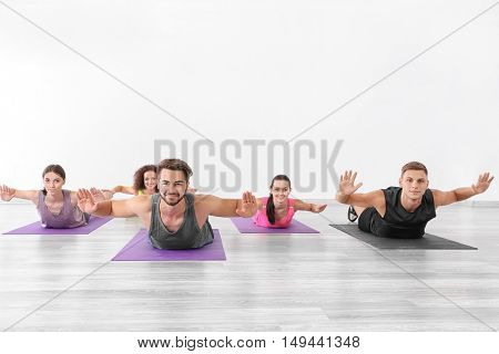 Group of people doing yoga exercises  in gym