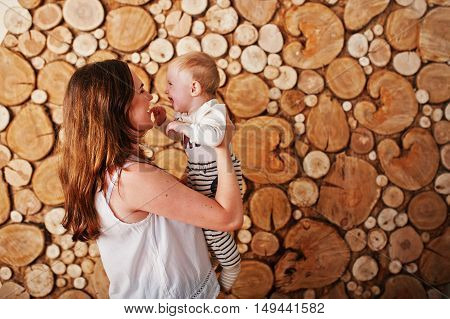 Happy Caucasian Mother Holding On Hands Her Baby Boy Background Stump Wooden Wall