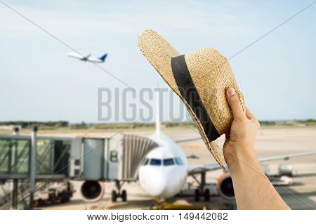 detail of hand holding the hat gesturing the greeting to the people of the flight of plane