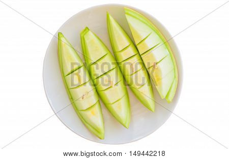 Juicy honeydew melon in a white dish isolated on white background Top view