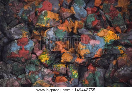 abstract background of the plane lying on colored stones close-up. Many stones painted with colored inks