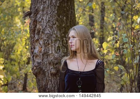 Blond Long-haired Girl In A Fantasy Black Dress In An Autumn Forest