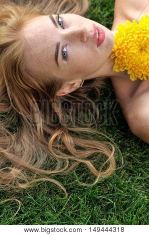 Girl Lying On The Grass With Yellow Flowers.