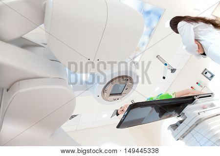 Doctor or nurse standing by a patient under modern medical x-ray oncology scanner in a hospital.