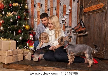 Happy family Christmas. Winter holidays at home. Family reading a book together.