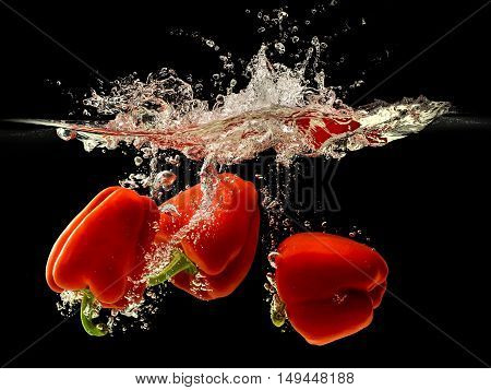Group of bell pepper falling in water with splash on black background.