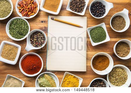 Various spices in bowl and blank notebook.