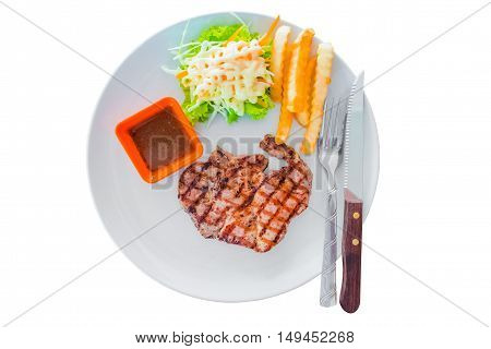 Pork steak served with crisp golden french fries and fresh salad accompanied by BBQ or tomato sauce isolated on white background.