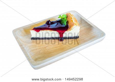 Slice of blueberry cheesecake with blueberries on wooden plate isolated on white background.