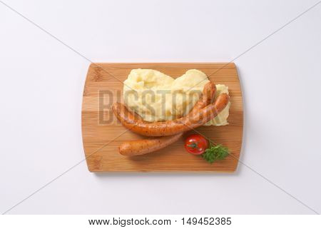long thin sausages with mashed potato puree on wooden cutting board