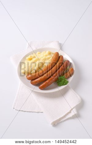 long thin sausages with mashed potato puree on white plate