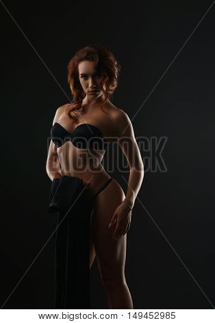 Image of hot red-haired woman posing in lingerie, on gray backdrop