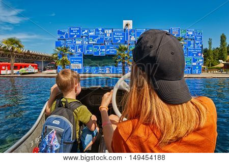 LUZERN, SWITZERLAND - 10 August 2016: Children enjoying boat ride in Swiss Museum of Transport with road signs as backdrop